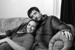 A happy young couple enjoy some cuddling on the couch.